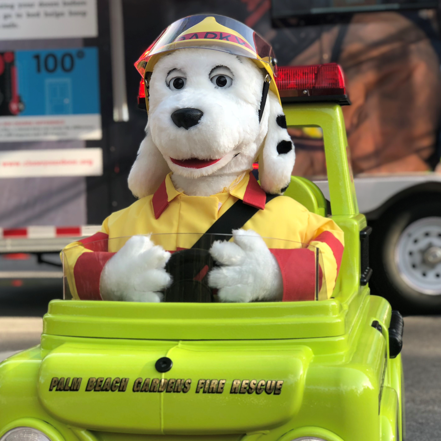 Sparky mascot in miniature fire engine