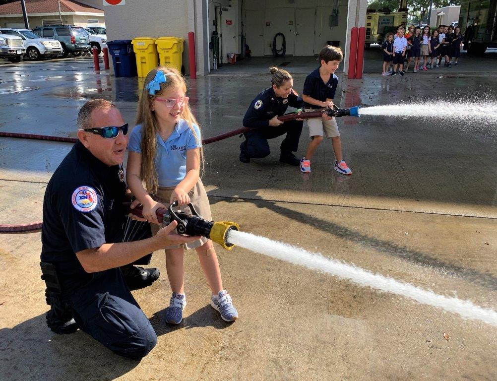 Firefighters Teaching Children to Use Fire Hose.