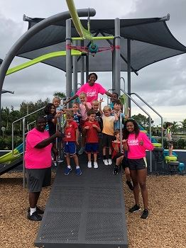 Young children and camp counselors standing on playground equipment.
