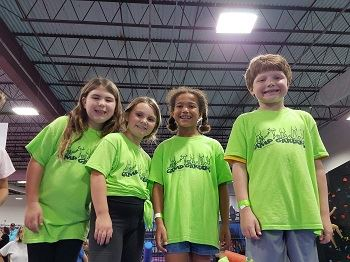 Four children in camp t-shirts