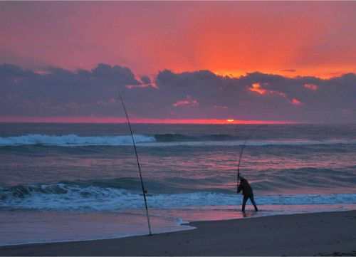 Photograph of a man fishing at sunrise.