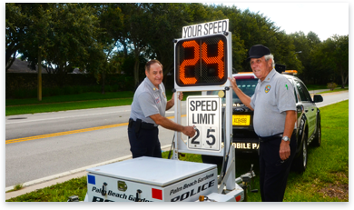 Two men setting up a speed limit sign