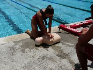 A female lifeguard performing CPR on a mannequin