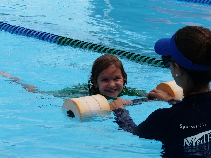 An instructor guides a young girl through the water with a flotation device during a swimming lesson