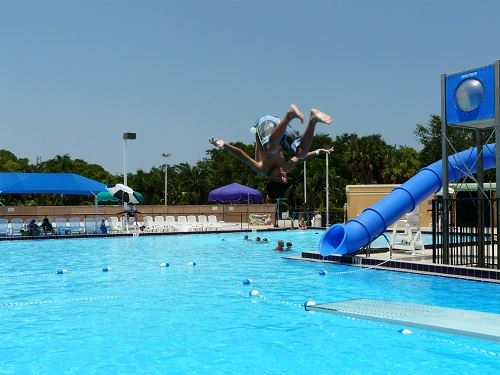 Main pool with slide and a boy doing a flip off the diving board