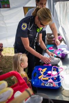 A Paramedic putting a bandage on a little girl's stuffed animal.