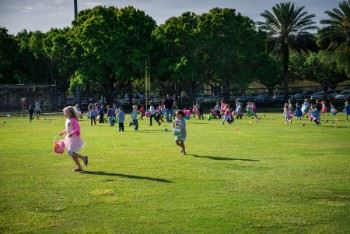 Children running on the field to find Easter eggs