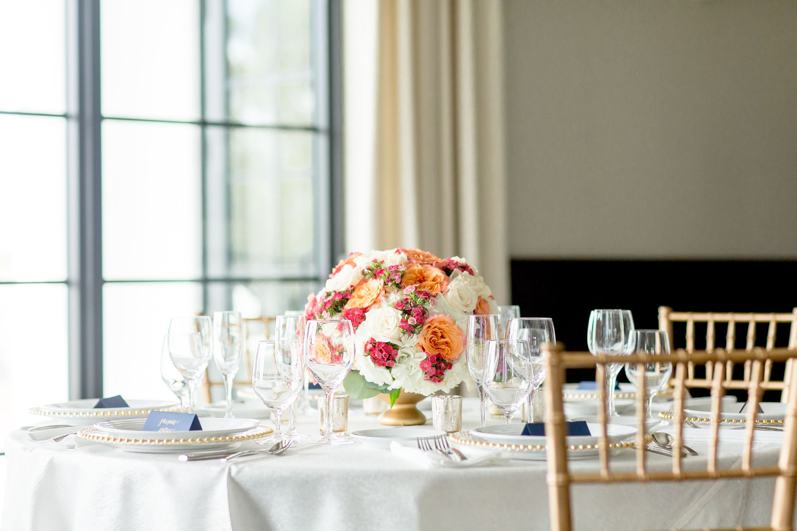 Flower centerpiece on table and gold chairs