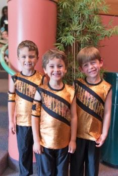 Three young boys in dance costumes.