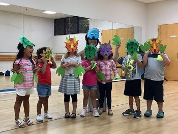 An instructor with young boys and girls wearing dinosaur masks.