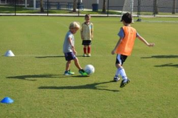 Three young boys kicking a soccer ball.