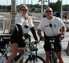 A female police officer and a male police officer smiling for a picture while on their bikes