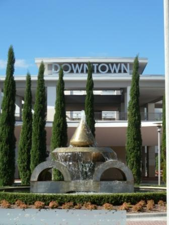 "Abstract fountain with sculpture design outside a building with word ""Downtown"" on building"