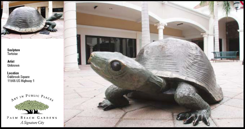 Statue of tortoise in open, brick-paved area
