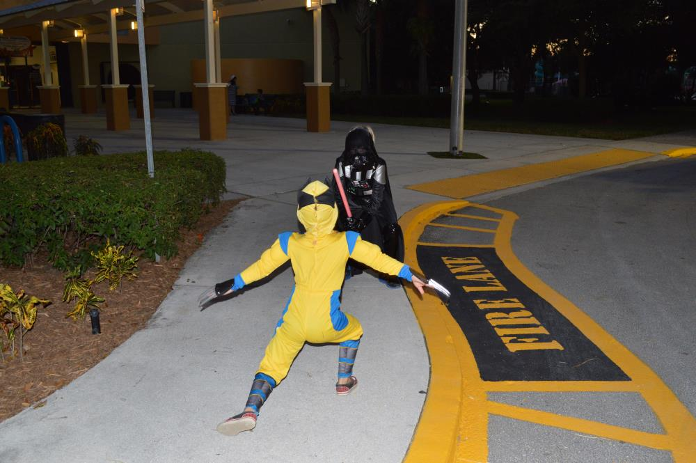 Kid dressed in Darth Vader costume points lightsaber at kid dressed as Wolverine as the two face each other