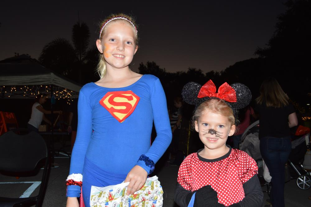 Girl dressed in blue superman outfit stands next to girl dressed in Minnie Mouse outfit